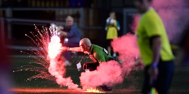 A security guard picks up a flare that was thrown onto the field during second half Canadian Championship...