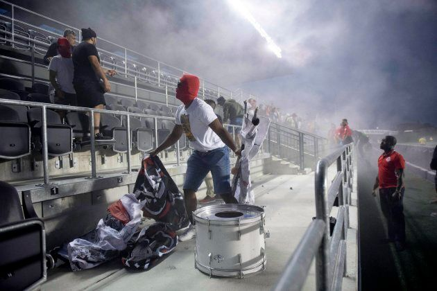 Toronto FC fans are ejected from the stadium after a flare was thrown onto the field during second half...