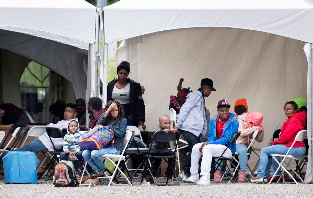 Asylum seekers wait to be transported to a processing centre after entering Canada illegally from the...