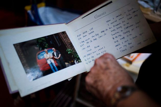 Elizabeth Hill looks through a guest book with notes from live-in students, in her home in Toronto, on July 20, 2018.