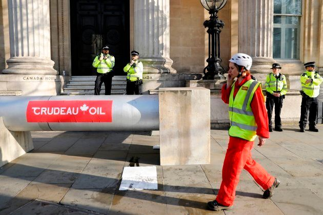 Demonstrators use a mock oil pipeline to block the entrance to the Canadian Embassy in central London...