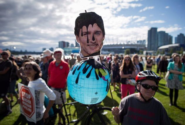 A protester holds a photo of Prime Minister Justin Trudeau and a representation of the globe covered...