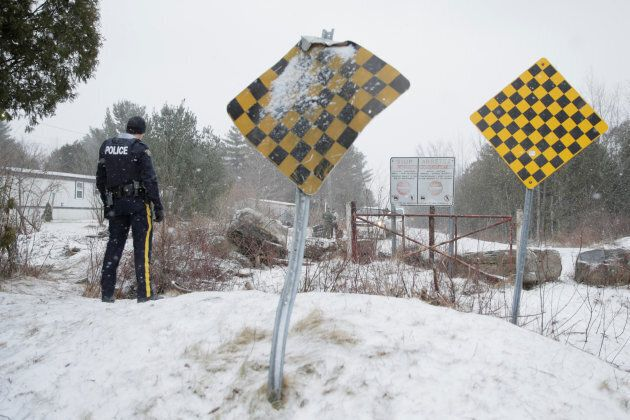 An RCMP officer watches as a man is checked by U.S. border patrol before he crossed the U.S.-Canada border into Hemmingford, Que. on March 2, 2017.