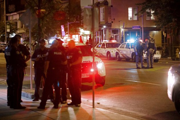 Toronto police officers walk the scene at Danforth Avenue on July 23,