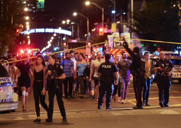 People leave an area taped off by the police near the scene of a mass shooting in Toronto on July 22,