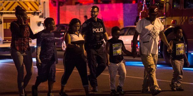 Police escort civilians away from the scene of a mass casualty incident in Toronto on Sunday, July 22,