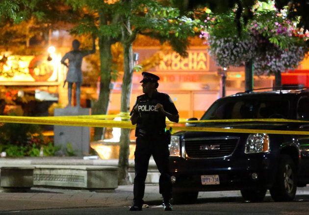 A police officer guards the scene of a mass shooting in Toronto, July 22,