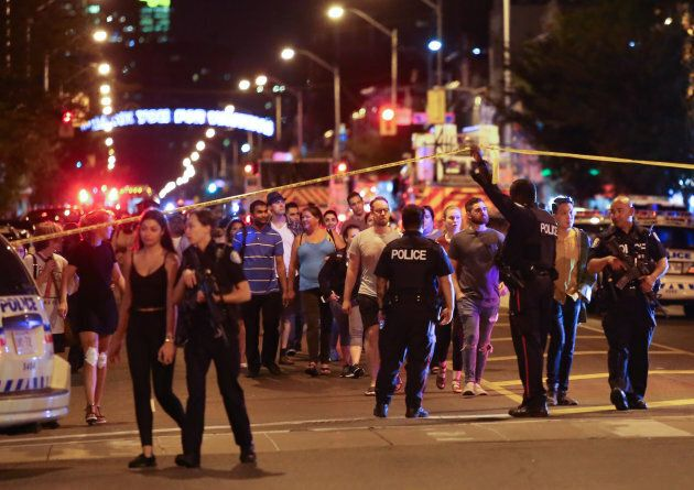 People leave an area taped off by the police near the scene of a mass shooting in Toronto on July 22, 2018.