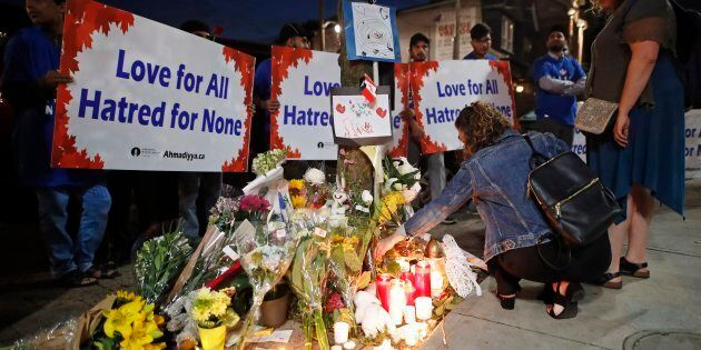 People place flowers and candles at a makeshift memorial remembering the victims of a shooting on Sunday...