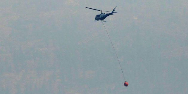 A helicopter battles a wildfire along the shore line of Highway 97 heading towards Summerland B.C. on...