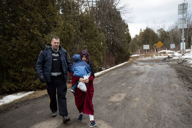 A mother and child from Turkey are escorted by RCMP after they crossed the U.S.-Canada border into Canada,...