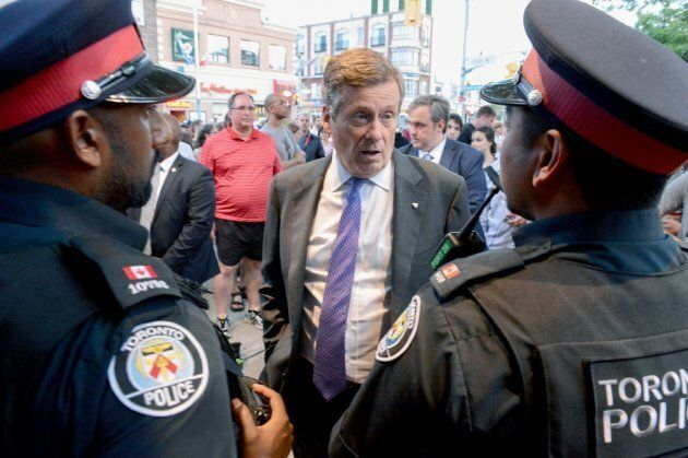Toronto Mayor John Tory speaks to police officers at the scene following a mass shooting in Toronto on...