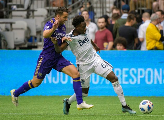 RJ Allen (27) of Orlando City (L) and Alphonso Davies (67) of the Vancouver Whitecaps fight for the ball...