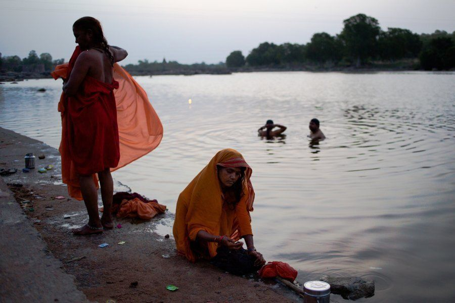 Indian women wash their saris on the banks of the Betwa River in Orchha in the state of Madhya Pradesh...