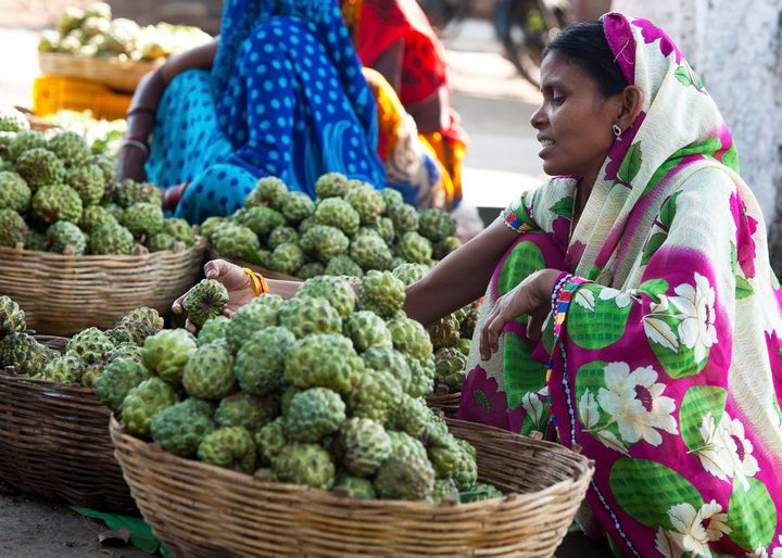 A woman sits at a roadside market in a Madhya Pradesh town in India.