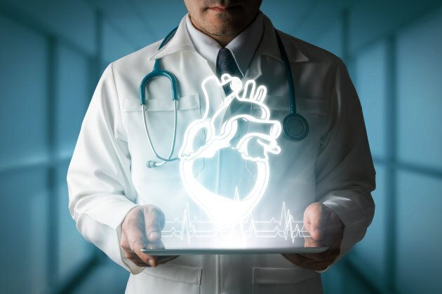 Medical Concept - Doctor showing heart hologram generated from tablet
