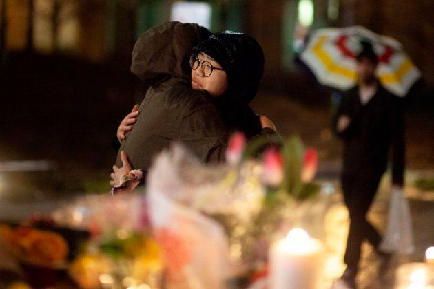 Mourners share a hug during a candle light vigil near the site of the deadly Toronto van attack in