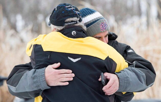 Humboldt Broncos' Adam Herold's father Russell receives a hug as friends and family celebrate what would...