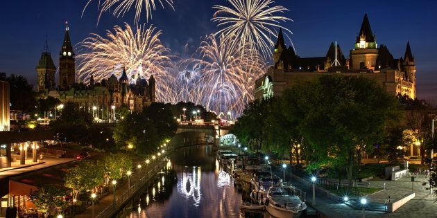 Fireworks are visible from the Rideau Canal in Ottawa, with Parliament Hill and the Fairmont Chateau...