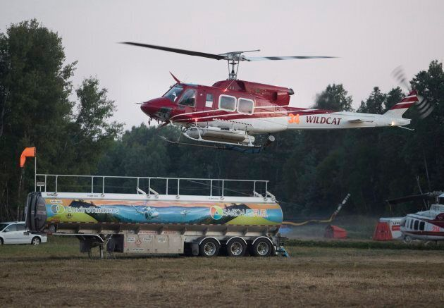 A firefighting helicopter lifts off from the command centre and base camp in Britt, Ont. on