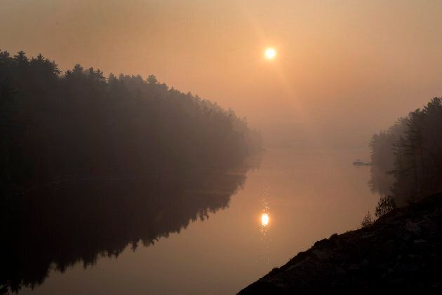 The French River, near Killarney, Ont., is shrouded in smoke from an active forest fire nearby on