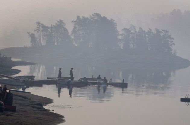Smoke blankets the area as Ministry of Natural Resources firefighters work a boat at Flat Rapids Camp...