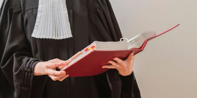 canadian lawyer in toga, reading from a red law