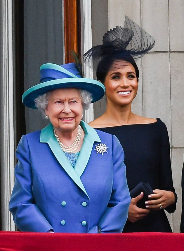 Queen Elizabeth ll and Meghan, Duchess of Sussex stand on the balcony of Buckingham Palace to view a...