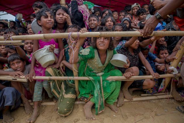 Rohingya Muslim children, who crossed over from Myanmar into Bangladesh, wait pressed against each other...
