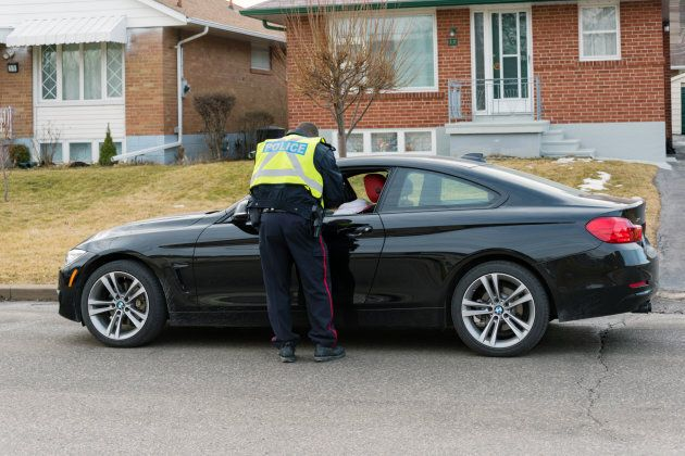 A Toronto Police Service officer giving a speeding ticket to a driver parked on the side of the road...