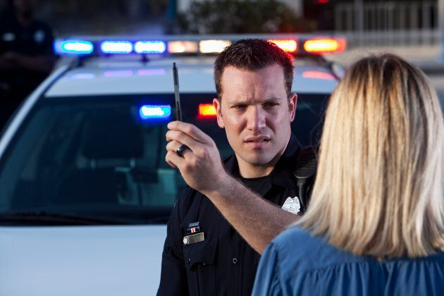 Police officer (20s) conducting sobriety test on woman.