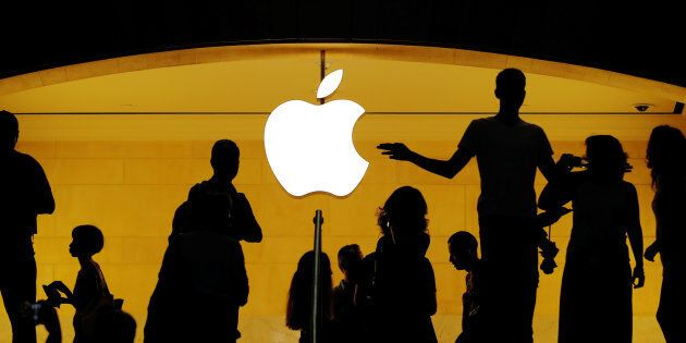 Customers walk past an Apple logo inside an Apple store at Grand Central Station, New York, N.Y., Aug....