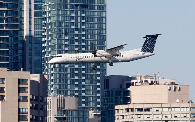 A Porter Airlines aircraft passes buildings in downtown Toronto as it prepares to land at Billy Bishop...