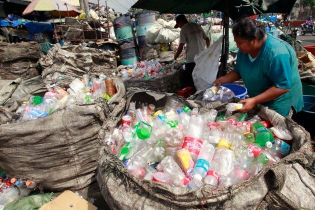 People sort through plastic bottles they collected and are about to sell at a junk shop in Manila on...