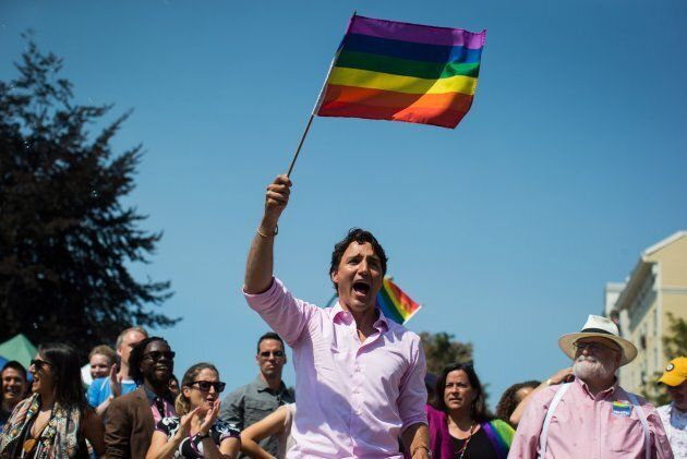 Justin Trudeau waves a rainbow flag while marching in the Pride Parade in Vancouver on Aug. 5, 2018.