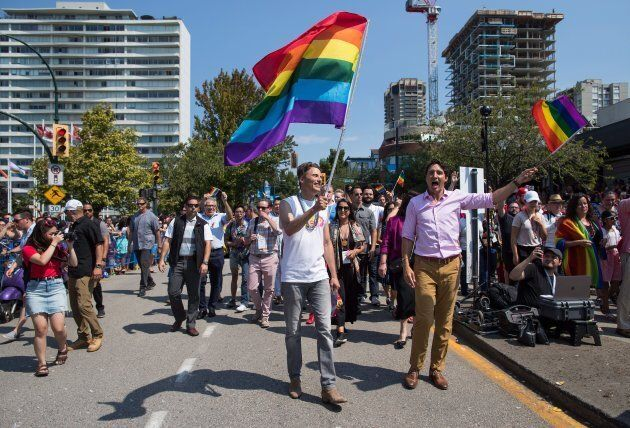 Justin Trudeau, right, and Vancouver mayor Gregor Robertson, centre, march in the Pride Parade in Vancouver, on Sunday August 5, 2018.