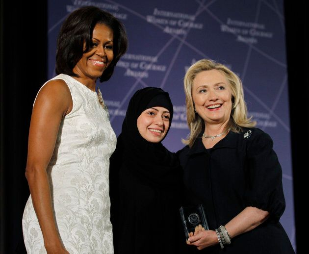 U.S. Secretary of State Hillary Clinton and First Lady Michelle Obama congratulate Samar Badawi during the State Department's 2012 International Women of Courage award winners ceremony in Washington on March 8, 2012.
