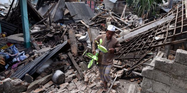 A man carries a small bicycle through the ruins of houses damaged by an earthquake in West Lombok, Indonesia...