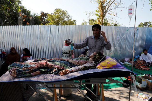 A man makes phone calls next to an injured villager outside of Tanjung hospital, after earthquake hit...