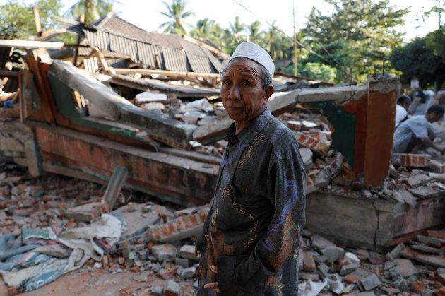 A villager walks through a collapsed house after an earthquake hit Lombok Island in Pemenang, Indonesia...