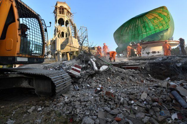 Indonesian search and rescue personnel work on a collapsed mosque in Pemenang, North Lombok on Monday,...