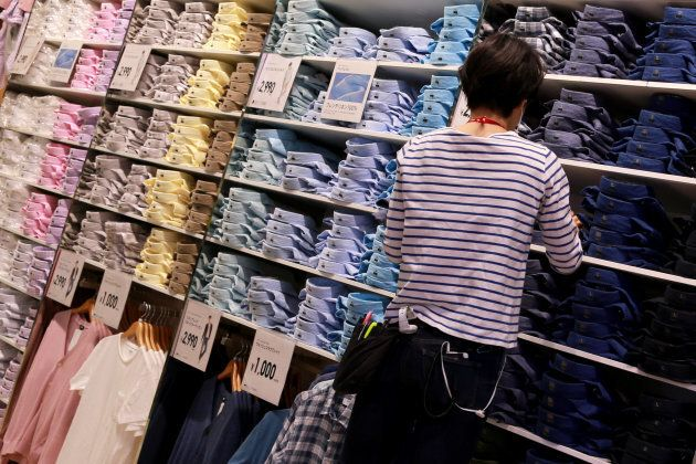 An employee folds shirts on display at the flagship Uniqlo store in Osaka, Japan, on April 11,