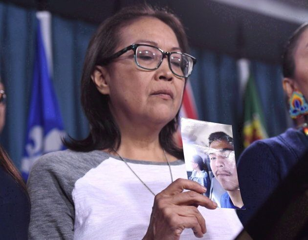 Debbie Baptiste, mother of Colten Boushie, holds a photo of her son during a press conference on Parliament...