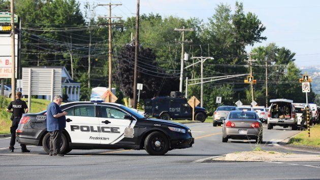 Police officers survey the area of a shooting in Fredericton, N.B. on Aug. 10,