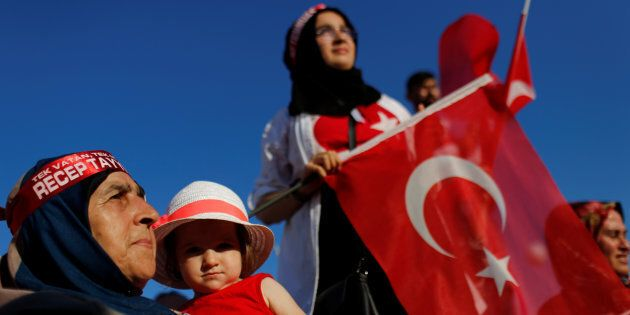 People wave Turkey's national flags and portraits of Turkish President Recep Tayyip Erdogan as they arrive...