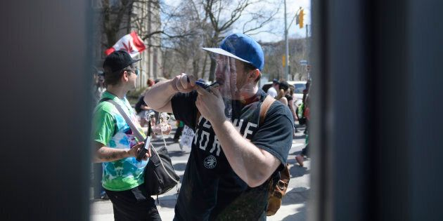Reflection of a participant lighting a pipe during the Toronto Global Marijuana in spring