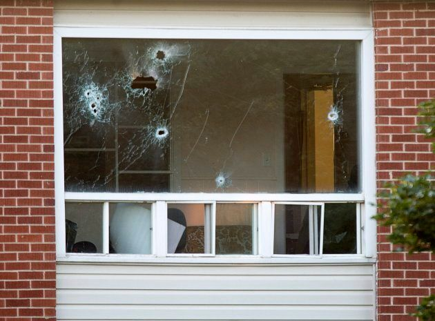 Bullet holes riddle a window in an apartment building in Fredericton on