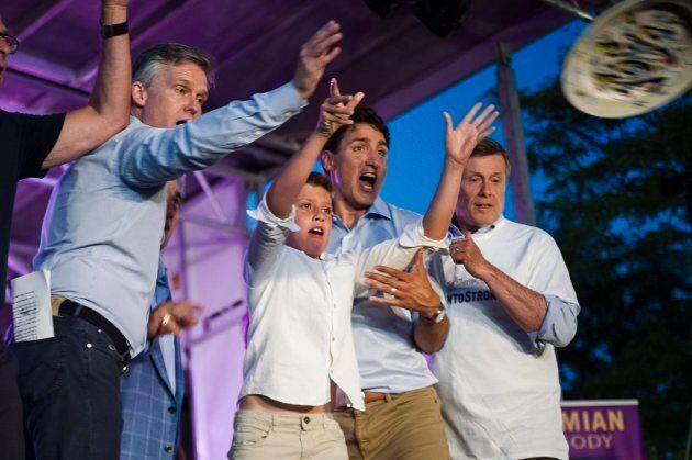 Prime Minister Justin Trudeau helps son Xavier, centre, to throw a plate alongside Toronto Mayor John...