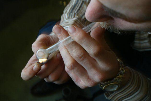 An Australian man smoking crystal meth from a