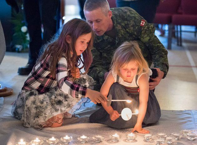 Residents attend a candlelight vigil at St. John the Evangelist Anglican Church, in Fredericton on Friday,...